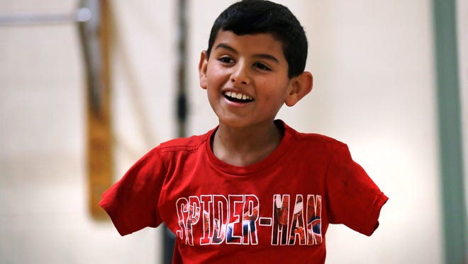 "Syrian refugee Ahmad Alkhalaf smiles while playing with friends during a day camp for local Muslim children in Sharon, Mass. ""Anything is possible in this world. You just have to believe in yourself,"" says Ahmad, whose arms were blown off above the elbows in a refugee camp bomb blast in 2014, which also killed three of his brothers. (AP Photo/Charles Krupa)"