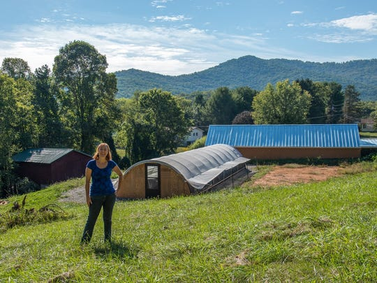 MR Gardens Owner Megan Riley on her farm in Oakley. A hoop house for additional plant storage is next to the passive solar greenhouse in the background.