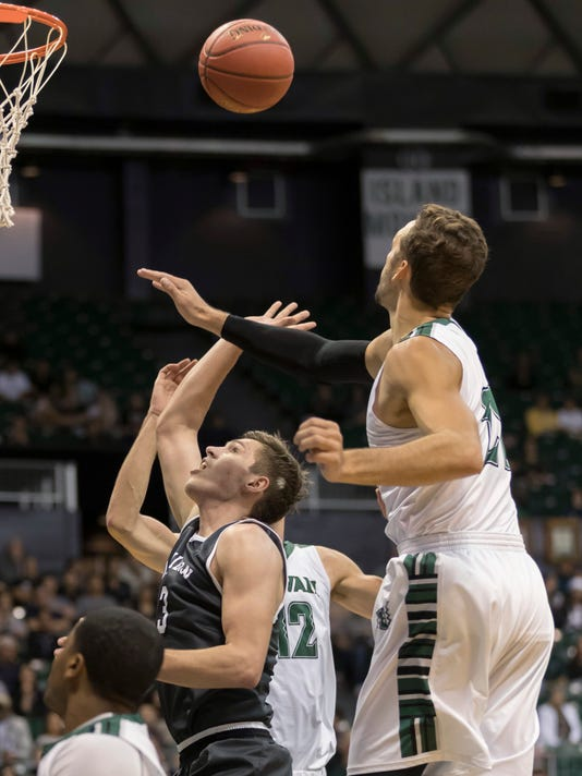 Davidson guard Jon Axel Gudmundsson, center, has his shot blocked by Hawaii forward Gibson Johnson, right, during the first half of an NCAA college basketball game at the Diamond Head Classic tournament, Saturday, Dec. 23, 2017, in Honolulu. (AP Photo/Eugene Tanner)p