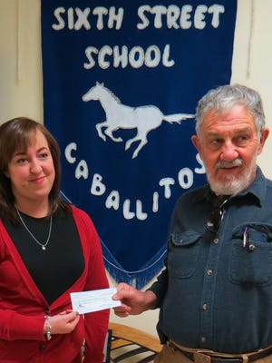2015 Grant County Art Guild president Tom Vaughan presents a check for additional art supplies to Sixth Street Elementary School art teacher Lydia Burns.