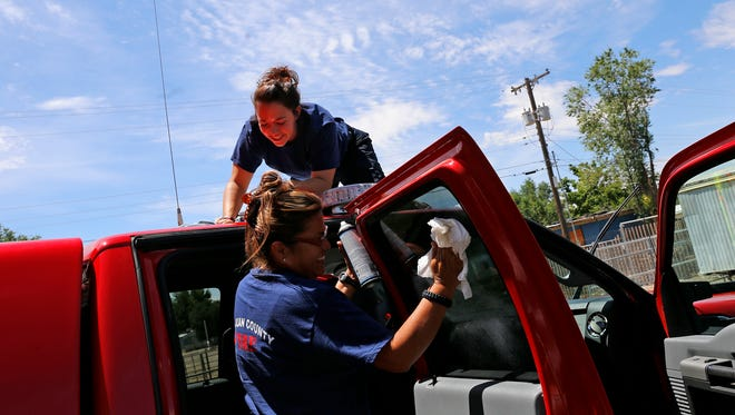 Jessica Kaufman, with San Juan County District 6 Emergency Medical Services support, at top, and firefighter Clarissa John  help clean their department's truck on Monday at San Juan County's Lee Acres Fire Department District 6 in Farmington. San Juan County officials are considering adding fire stations to improve service and lower residents' insurance premiums.
