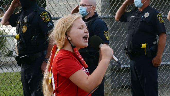 Avery Horan, 11, of the Groton Mystic District 10 Fall Ball Softball League, sings the national anthem on Friday near Ledyard and State police to honor those who died on 9/11. Ava Boenig, of the Preston team, read a 9/11 poem before the two teams took the field at Preston Community Park. See videos and more photos at NorwichBulletin.com