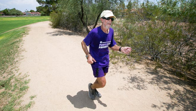 Hal Gensler, of New River, runs 90 laps around Mescal Park to commemorate his 9,000th consecutive day of running at least one mile on Friday, July 25, 2014.
