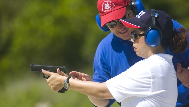 FBI Agent and Principal firearms instructor Ken Klocke guides Anita Borja Enriquez in firing a 40-caliber pistol during the final session of the FBI Citizens' Academy at the Andersen Air Force firing range on May 16, 2009.