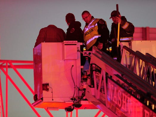 Police and fire talk a man off a sign above Interstate