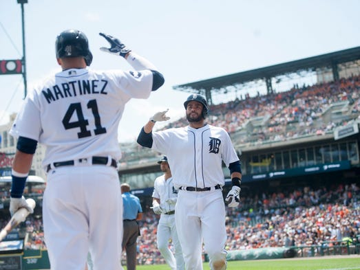 Detroit right fielder J.D. Martinez, right, gets a