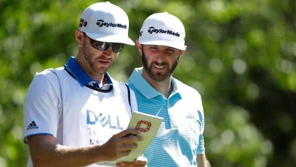 Dustin Johnson, right, goes over the yardage book with