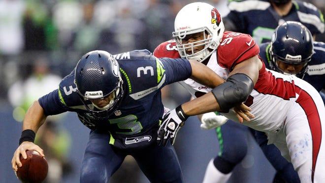 Dec. 22, 2013: Arizona Cardinals defensive end Calais Campbell (93) sacks Seattle Seahawks quarterback Russell Wilson (3) during the fourth quarter at CenturyLink Field.