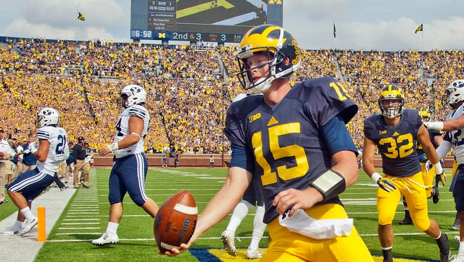 FILE - In this Sept. 26, 2015, file photo, Michigan quarterback Jake Rudock (15) celebrates his touchdown in the first quarter of an NCAA college football game against BYU in Ann Arbor.