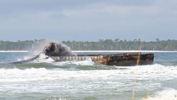 Tugboats work to remove stranded coal barge from Fort Pickens sandbar
