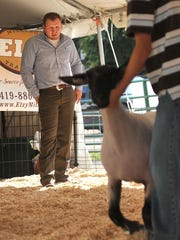 Duane Swank judges the junior showmanship of sheep round Wednesday evening during the first day of the Bellville Street Fair.