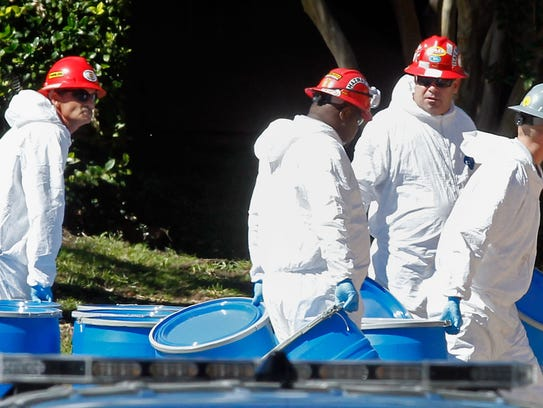 Hazmat workers with Protect Environmental unload barrels