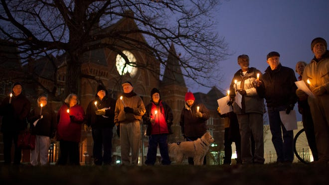 About fifty people gathered at Washington Park to participate in the annual Homeless Memorial Day candle light vigil Friday, December 19, 2014 that remembers the 39 homeless people, who died on the street this year.