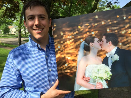Brian Siskoy, 28, shows a photo of his wedding to Camille DaDamio, 25.