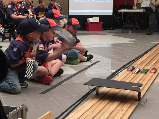 Scouts from metro Detroit watch their handmade cars race down the track during the pinewood derby May 16, 2015, at the Automotive Hall of Fame in Dearborn.