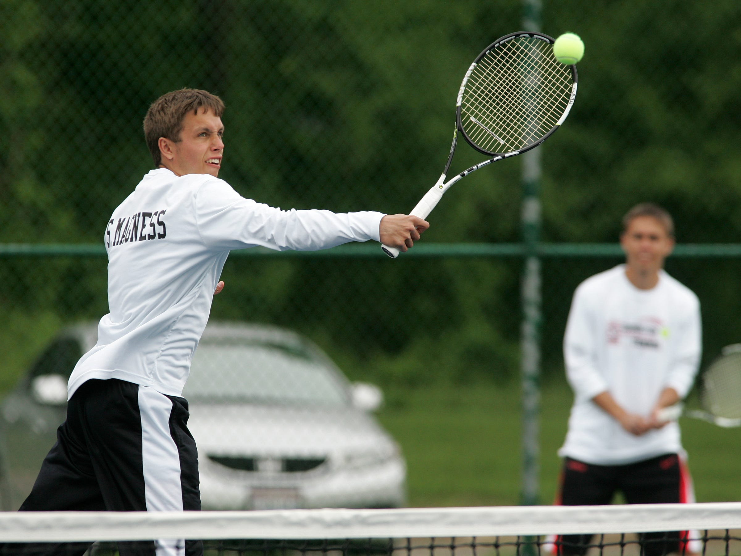 Sam Magness, left, and Jim Magness practice together as a doubles team Thursday at Coshocton High School. The brothers will be defending their district title at Ohio University.
