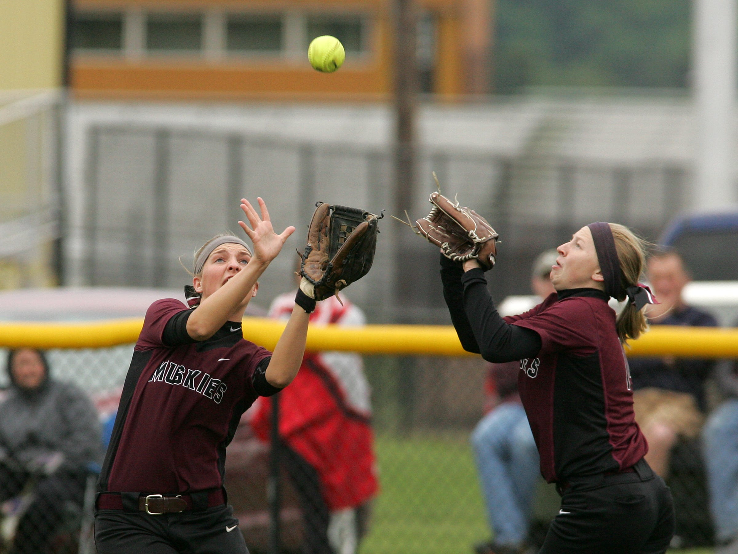 John Glenn senior MacKenzie Prater, left, and junior Lexi Baker, cover a fly ball to right center field Thursday during the team's 4-1 loss to Dover in the Division II district final at River View High School.