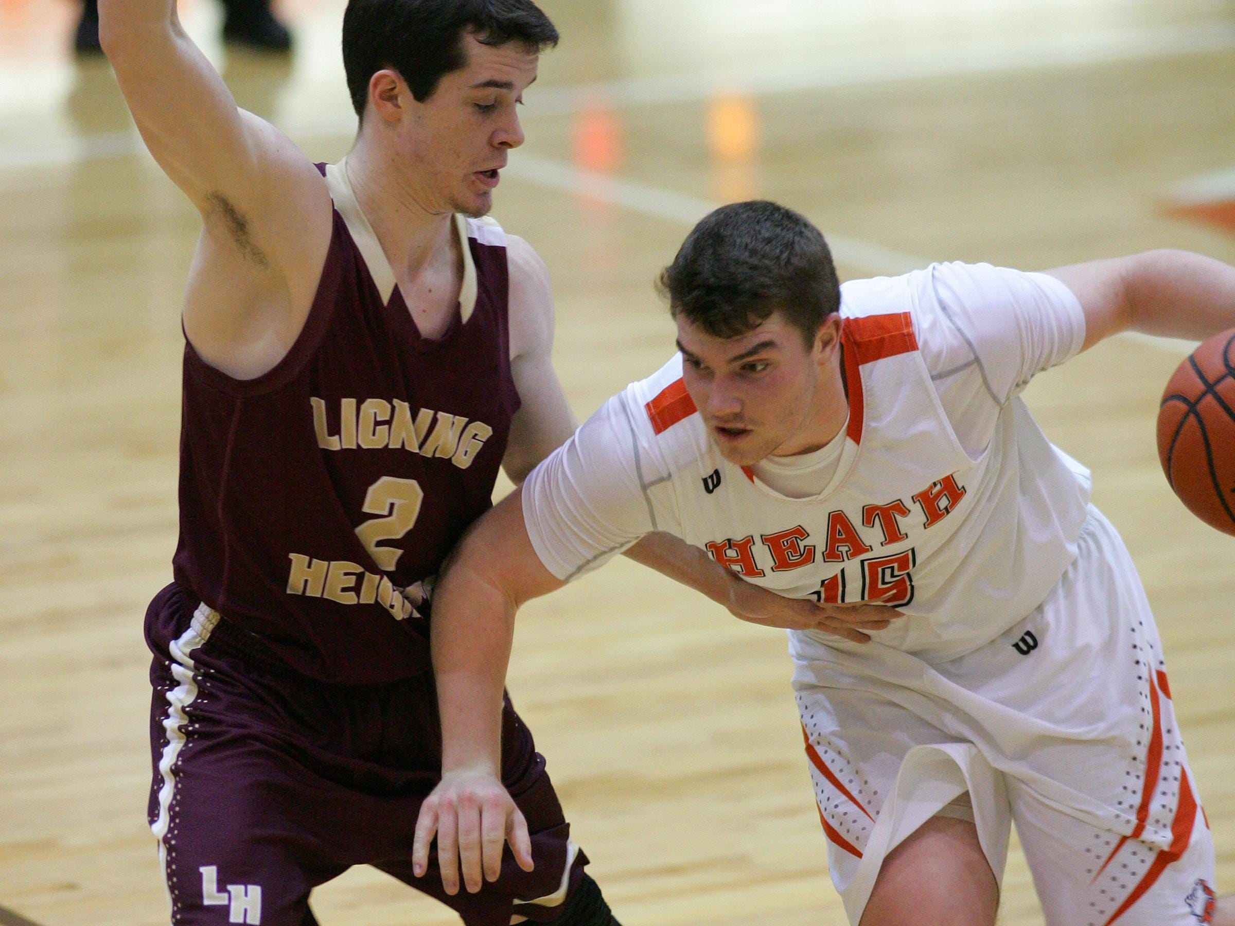 Heath's Payton Booth drives to the basket against a Licking Heights defender during a 2014-15 game.