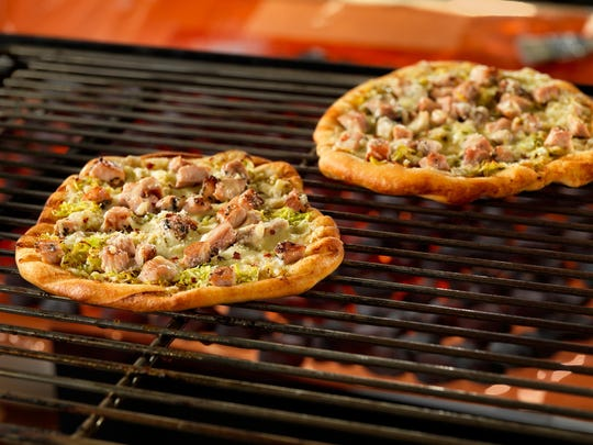 Grilled pizzas are topped with grilled herbed pork, fontina and Parmesan.