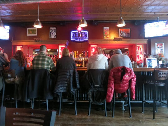 Rock show posters and a color-changing lighted logo add color to the wall behind the bar at the new Zeke's Rock & Roll BBQ in Ferndale.