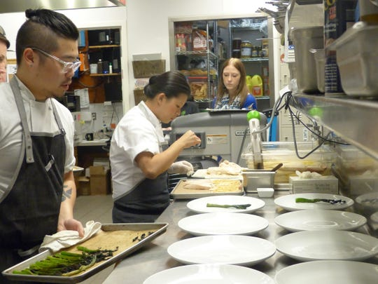 "Dearborn native Mei Lin, center, shown here cooking recently as a guest at the Root Restaurant & Bar in White Lake, will appear Wednesday night in the final round of Bravo TV's ""Top Chef"" cooking series."