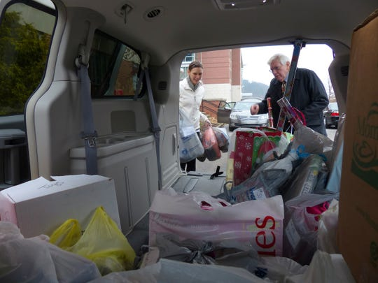 Mansfield University volunteers load up a van at the campus with gifts for Santa's Gift Bag in Mansfield. The items were taken to the Mansfield Fire Hall.