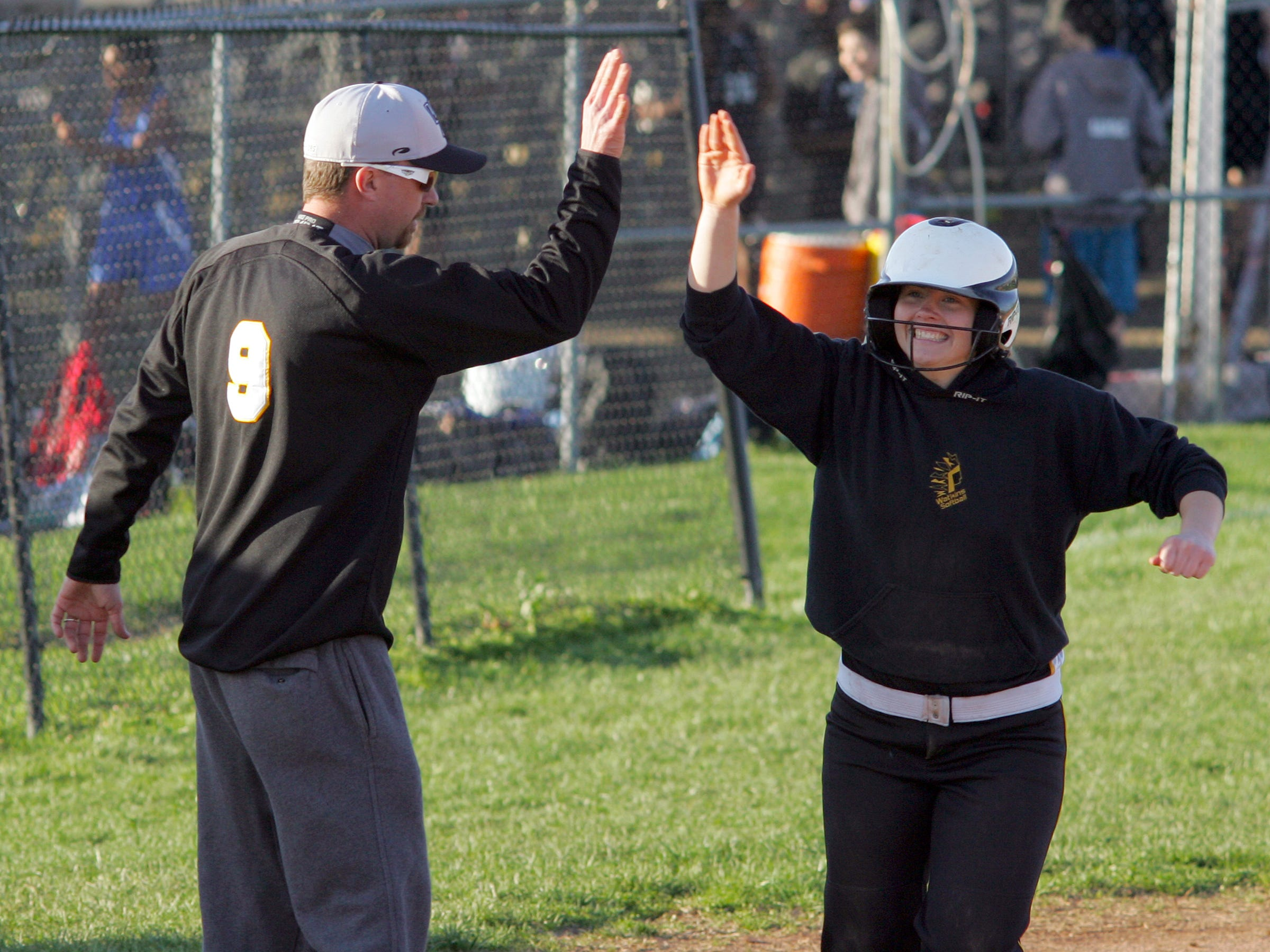 Watkins Memorial's Anna Shroyer high fives coach Mike Jellison after hitting a home run this past Friday during the team's 14-11 victory against Licking Heights.