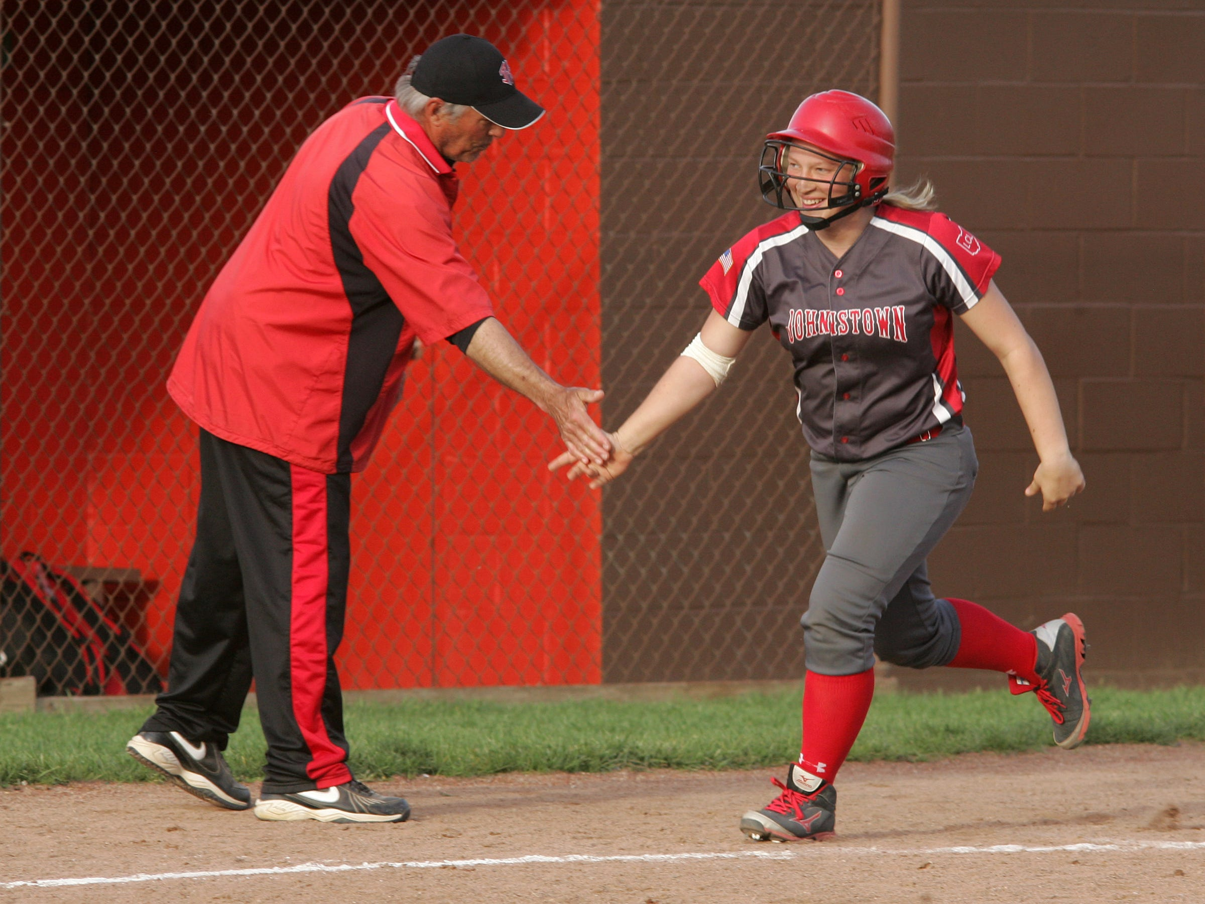 Johnstown junior Erin McConnell receives a low-five from coach Steve Smith after hitting a home run during Friday's fifth inning against Heath to help the Johnnies to a 14-4 victory in six innings.