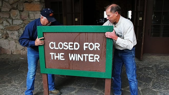 "Maintenance worker John Helms, left, and Mike Walters, maintenance manager, put out the ""closed"" sign as the Grand Canyon Lodge at the North Rim is prepares for it's annual winter closure."