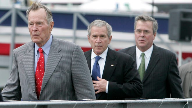 Then U.S. President George W. Bush (center) walking with his father, former president George H.W. Bush (left), and his brother, then Florida Governor Jeb Bush in October 2006.