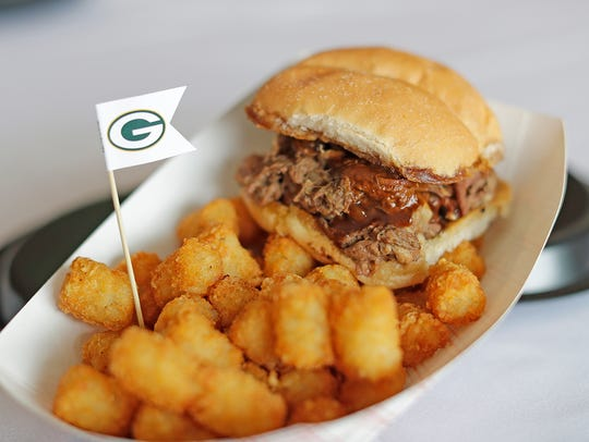 Pot roast sandwich served with tater tots.