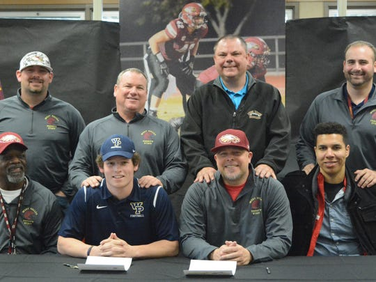 West Valley High's Graham Carnahan, second from left in front row, poses with coaches after signing to play football for William Penn University in Iowa.