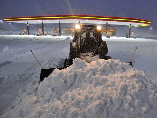 Plows work to control the snow from the blizzard on