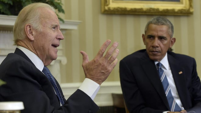 President Barack Obama listens as Vice President Joe Biden speaks in the Oval Office of the White House in Washington about the release of the Cancer Moonshot Report on Monday, Oct. 17, 2016.