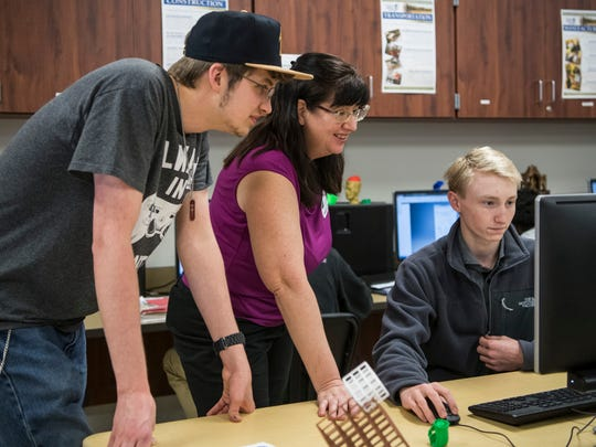 Ivy Tech student Andrew Meyer (left to right), Ivy Tech Professor Donna Zimmerman and North High School student Jacob Spurling discuss future plans for a prosthetic hand while using a computer-aided design software at North High School on Wednesday morning. Students from Ivy Tech and North High School's Project Lead the Way classes are collaborating to design and 3D print a prosthetic hand for an international organization called e-NABLE.