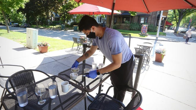 Rafael Rodriguez clears an outdoor table at Jines Restaurant on Rochester's Park Avenue last month.