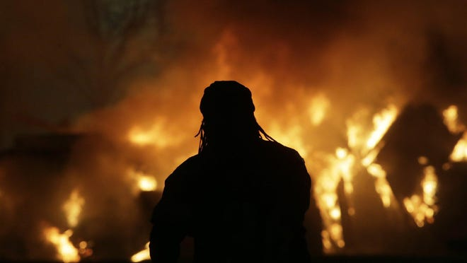 A man watches a fire burn on Oak Street near Fifth Street Downtown on Saturday, May 28, 2020.