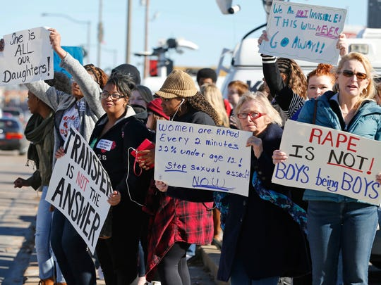 In this Nov. 24, 2014 file photo, students, parents and grandparents hold signs during a protest across the street from Norman High School in Norman, Okla.