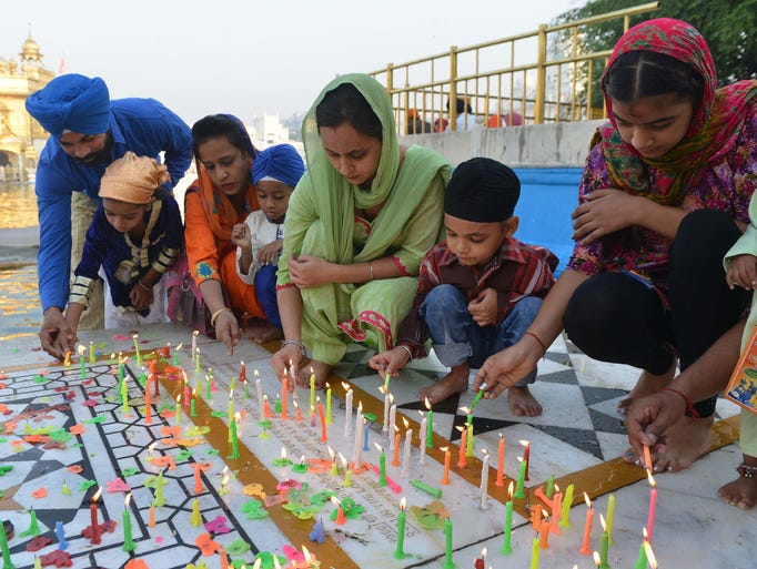 Indian Sikh devotees light candles in the early morning