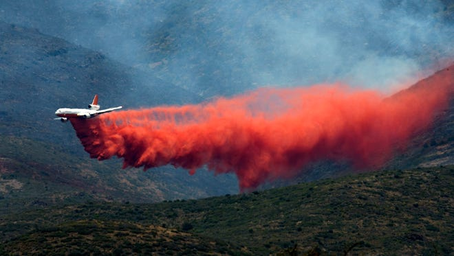 A DC-10 tanker plane drops fire retardant on the Tenderfoot Fire, as seen from Peeples Valley on June 10, 2016.