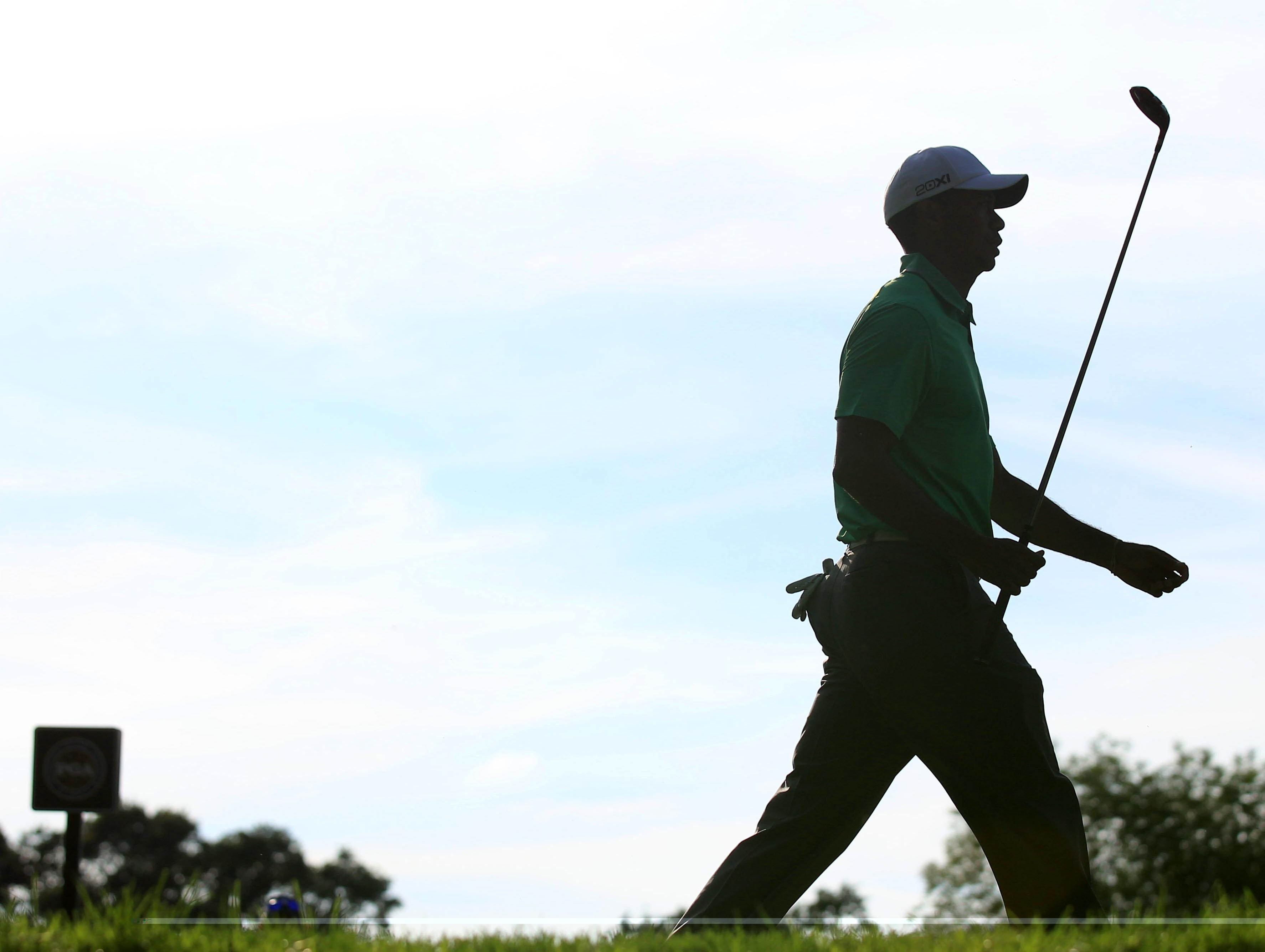 Tiger Woods walks off the 10th tee during Friday's second round of the 95th PGA Championship. Woods finished with an even par 70 to keep him at plus 1, eight strokes behind leader Jason Dufner's minus 9.