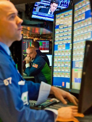 Virtu Financial traders review stock information at their trading bay computers at the New York Stock Exchange during early trading, Monday, Dec. 15, 2014, in New York.  U.S. stocks opened broadly higher Monday following the biggest weekly losses in two and a half years.