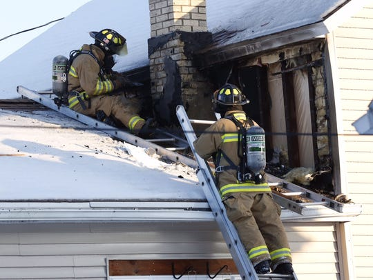 Members of the Waupun Fire Department work to put out