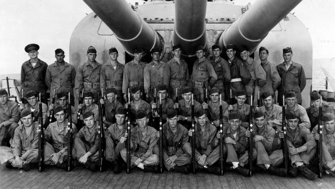 A Marine guard is shown under the turret of a gun on the deck of the USS Indianapolis.