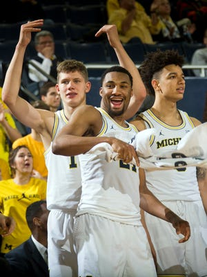 Michigan forward Moritz Wagner, left, guard Zak Irvin, center, and forward D.J. Wilson, right, cheer on their teammates in the second half of  the Wolverines' 97-53 win over Central Arkansas on Tuesday, Dec. 12, 2016 at Crisler Center.