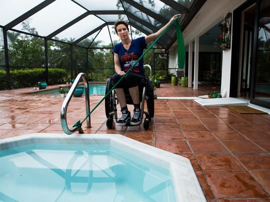 Edie Perkins stretches at her parent's house before training  for the Naples Daily News Half Marathon on her handcycle in the Naples Bath and Tennis Club neighborhood on Wednesday, Jan. 10, 2018.