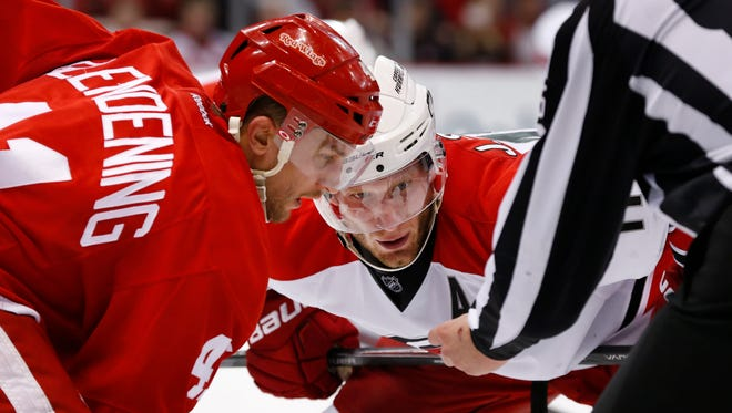 Carolina Hurricanes center Jordan Staal, right, and Detroit Red Wings right wing Luke Glendening watch the puck during a face-off April 7, 2015.