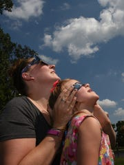 Erin Varilone helps her daughter iris, 3, with her