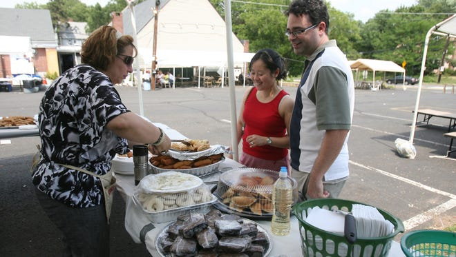 Nouha Habeiche of Franklin Park, left, serves up a plate of sweets for Kristine Van Tine and her husband Larry of Hamilton during the St. Sharbel Lebanese Festival in Somerset on 06/26/2010. Photograph by Andrew Miller/Courier News 11399