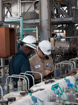 Operator Joseph Poole, right, checks the paperwork of an unidentified worker at the Chevron Phillips Chemical Co. midstream petrochemical facility in Baytown, Texas.